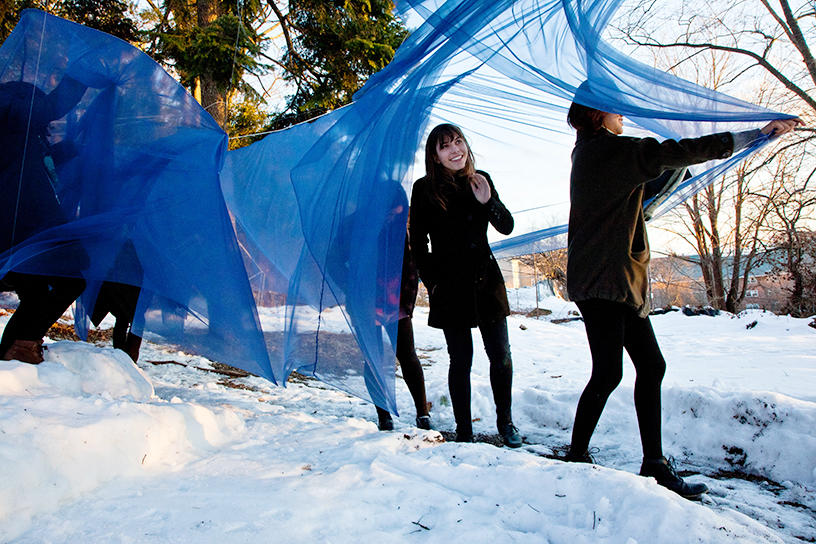 Students installing blue fabric sculpture outdoors in snow