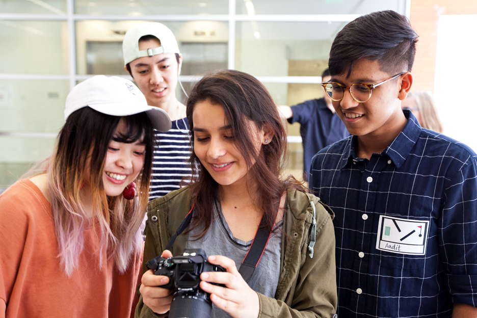 students looking at an image on a digital camera