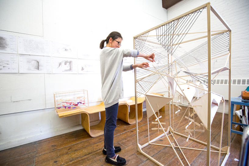 An Architecture student adding detail to tall wooden structure