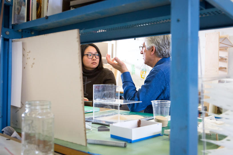 An Architecture student talking to a faculty member in the studio