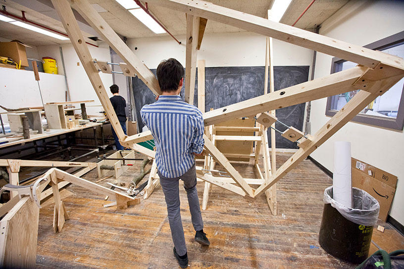 An Architecture student assesses a large angular wooded structure