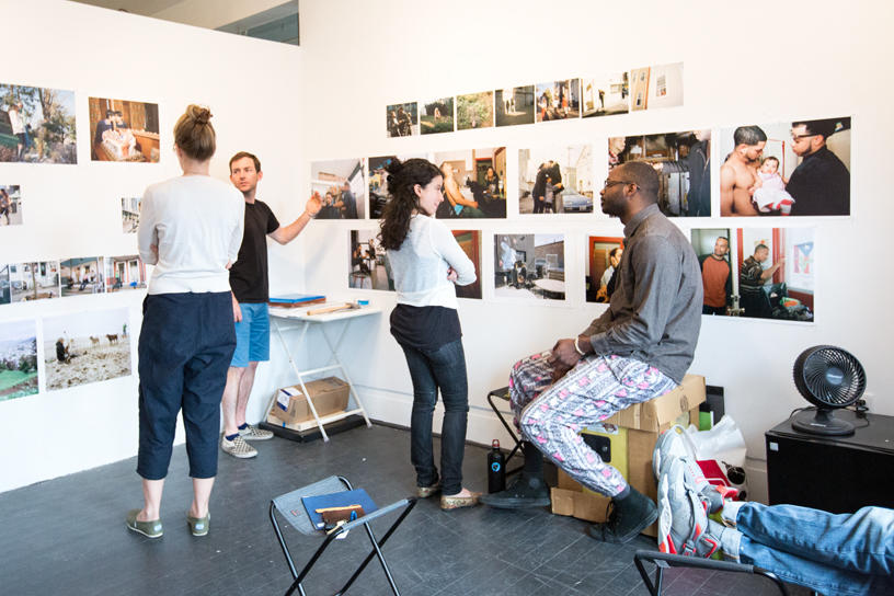Students sharing a discussion about photographs on the walls in the studio.