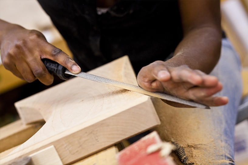A Furniture Design student hand-filing a block of wood