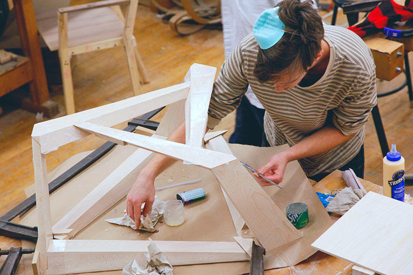 A Furniture Design student works in the studio