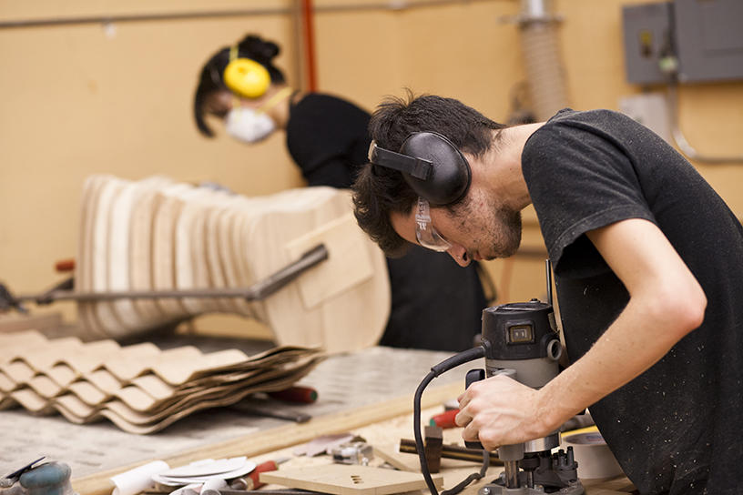 A Furniture Design student works with a router