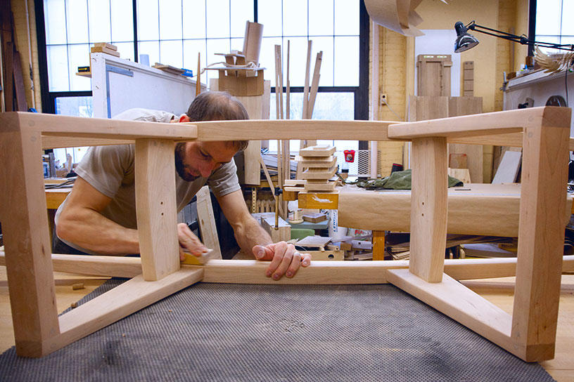 A Furniture Design student sands down a wooden structure
