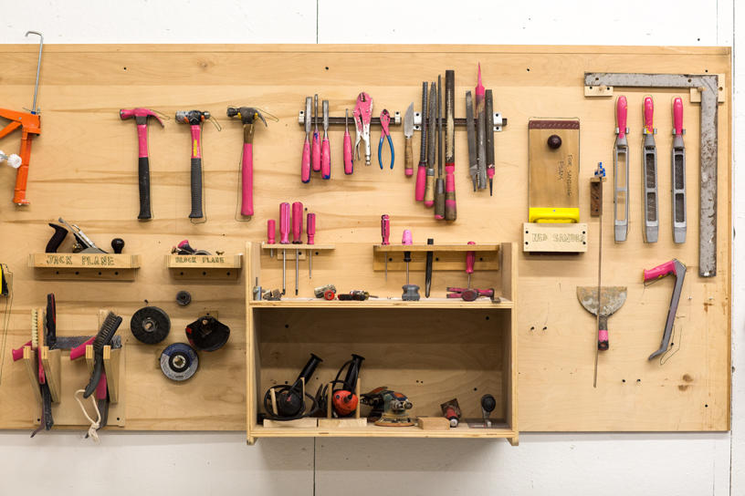 Several hand tools mounted onto a Furniture Design woodshop wall
