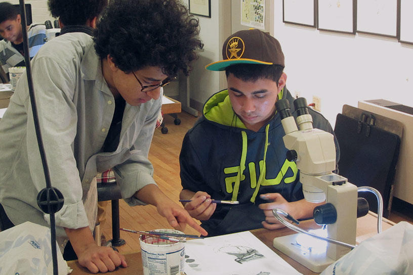 Instructor giving advice to a student painting a microscope