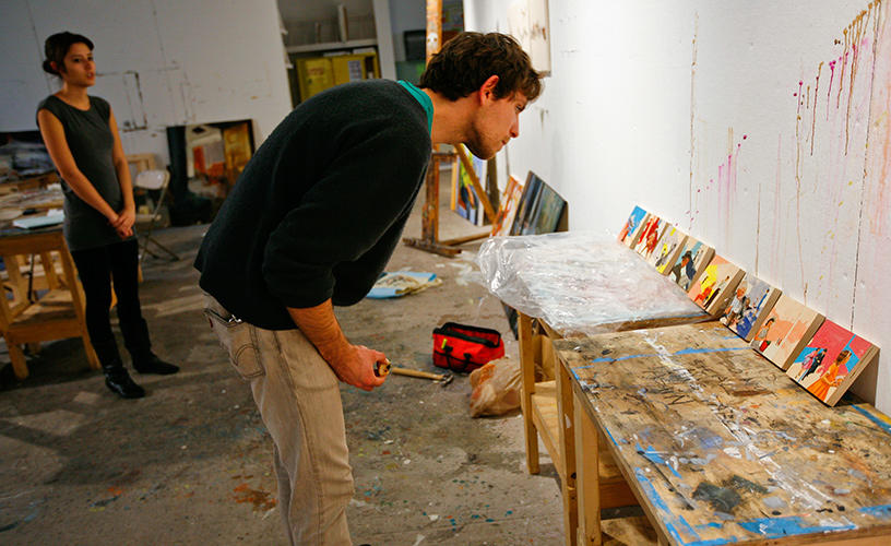 Person inspecting a row of small paintings