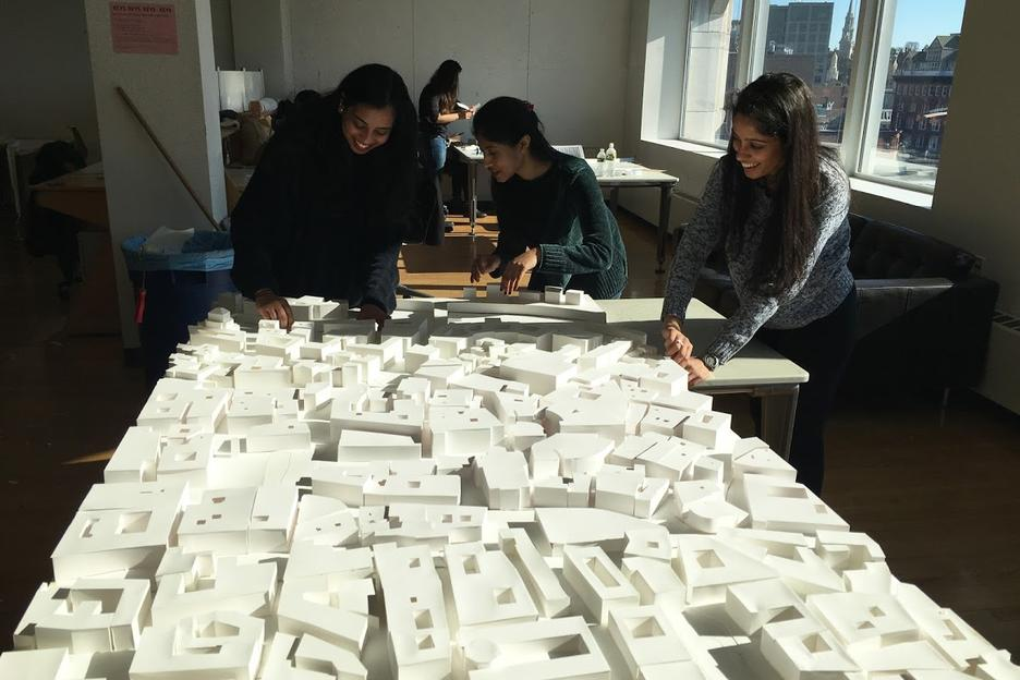 Interior Architecture students look at structural models on a long table