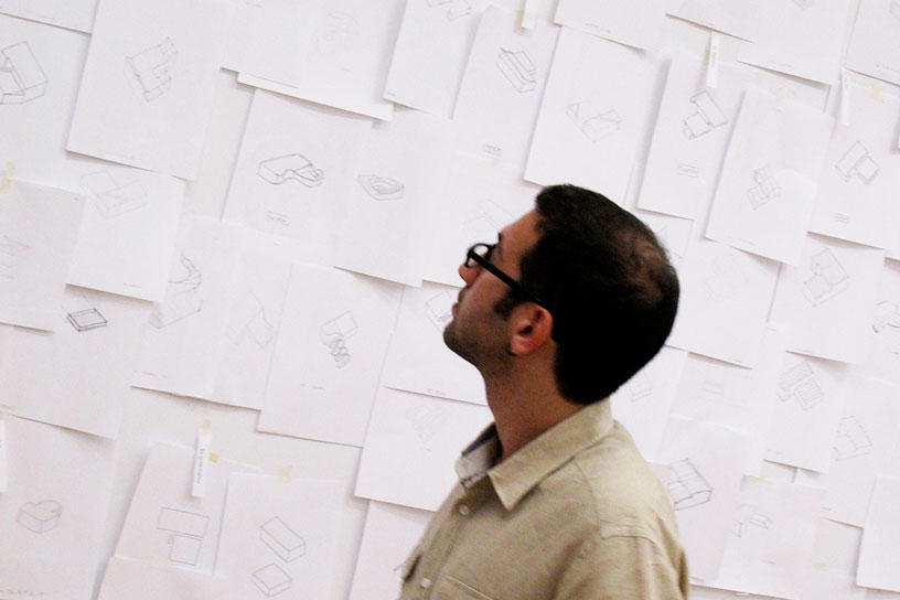 an Interior Architecture student looks at sketches on the wall