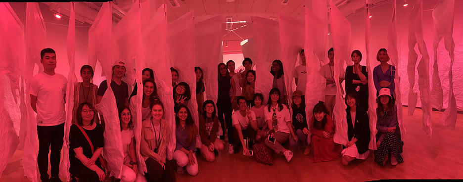 Interior Architecture students stand inside a red-lit, room-sized installation