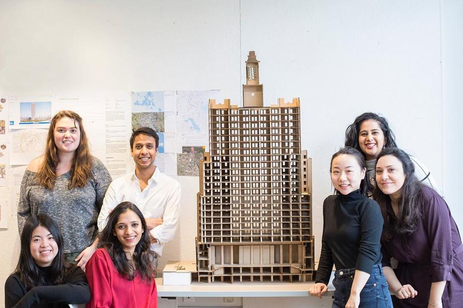 a group of Interior Architecture students stand aside a model of the 15 West building