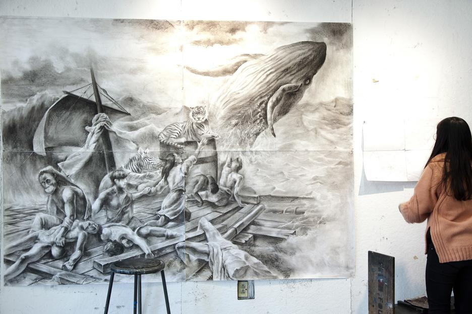 Large charcoal drawing of people on a raft in choppy waves with a whale