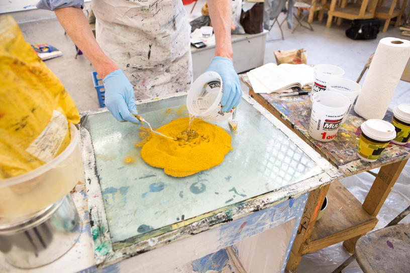 yellow pigment being mixed on a glass table