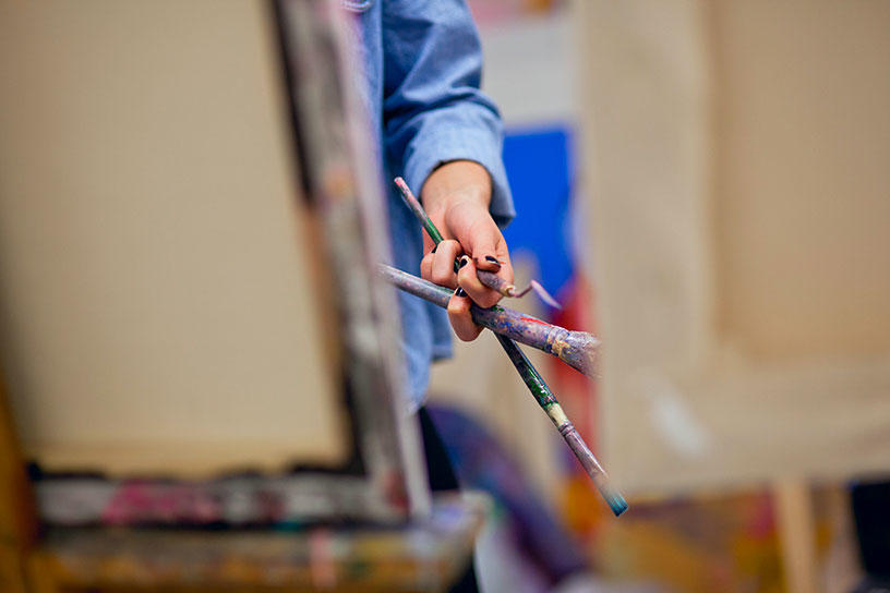 person painting on an easel while holding tools in their opposite hand