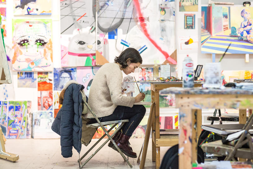 student sitting in a chair focused intently on their painting