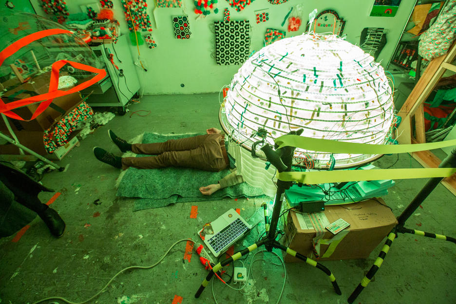 Student lying under an illuminated green sphere sculpture in the studio.
