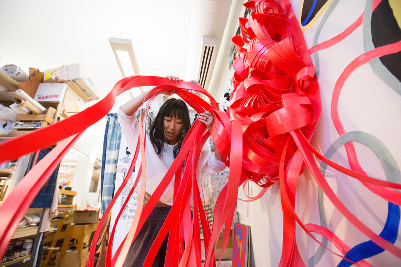 Student weaving large red ribbons.