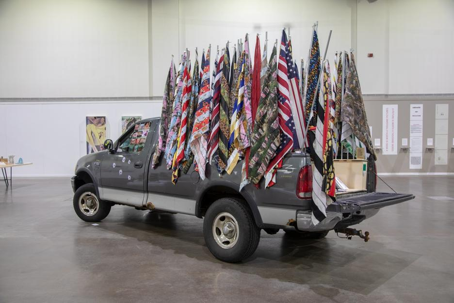 Student work by Erick Medel MFA 2018. A photograph of a pick-up truck on display in a gallery. The truck is decorated with bullet holes and poles holding up several dozen full-sized flags of varying colors and styles.
