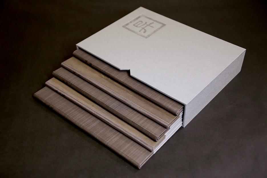 A set of five books coming out of a white book sleeve with a Chinese character in the upper right corner