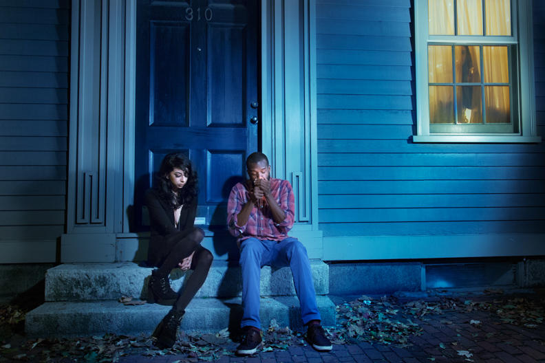 Student work by Jay Simple MFA 2018. A man and a woman share a cigarette while sitting on the steps outside of a house.
