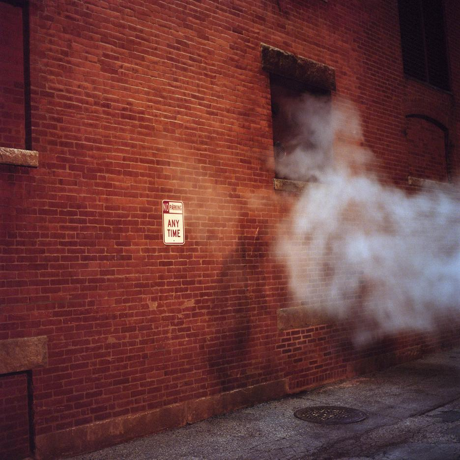 Student work by John Shen BFA 2019. Photograph of the side of a redbrick building in a steamy alleyway.