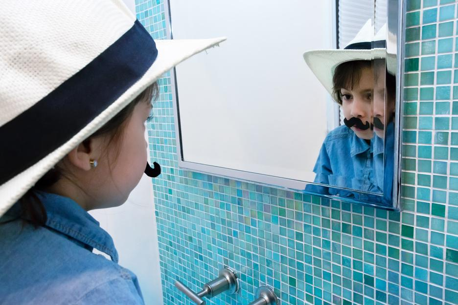 Student work by Maria Bedoya BFA 2017. Photograph of a child standing in front of a mirror wearing a fedora hat and a fake mustache.
