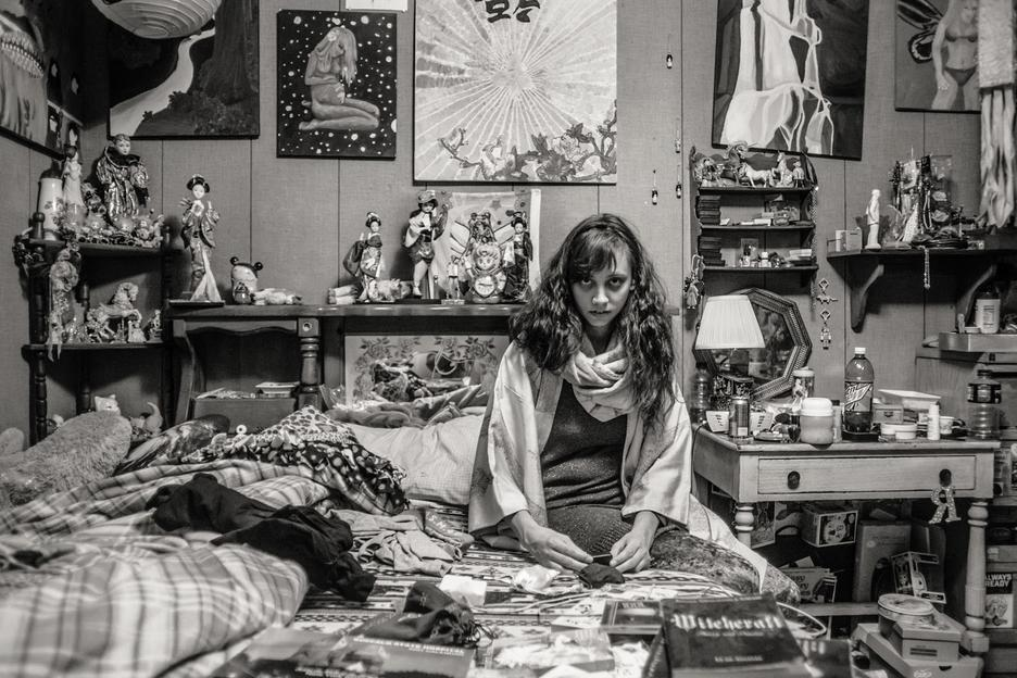 Student work by Matthew Barbarino BFA 2018. Black and white photograph of a girl sitting in a bedroom, surrounded by trinkets and art.