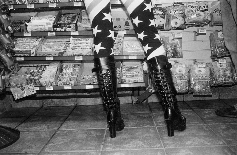 Student work by Matthew Barbarino BFA 2018. Black and white photograph of a woman's leggings and boots as she stands in front of a store counter.