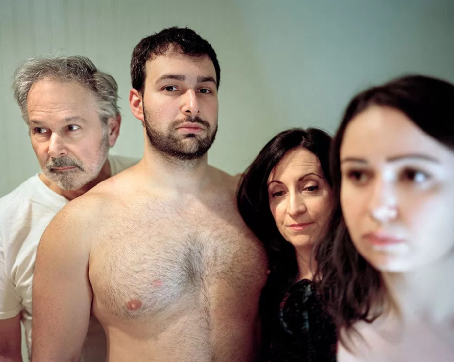 Student work by Nicole Schwartz MFA 2017. Photograph of a shirtless man standing next to his family members.