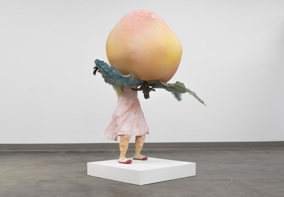 Student work by Renee Yu Jin BFA 2018. Sculpture of a girl carrying a giant sized fruit.
