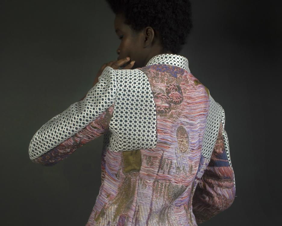 Student work by Talia Connelly BFA 2018. A man models a colorful custom jacket.