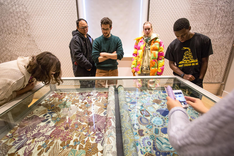 Students inspecting intricate museum textile.
