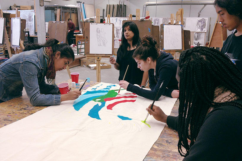 Students painting a large canvas together