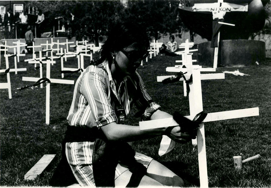 Person in a graveyard installing a cross